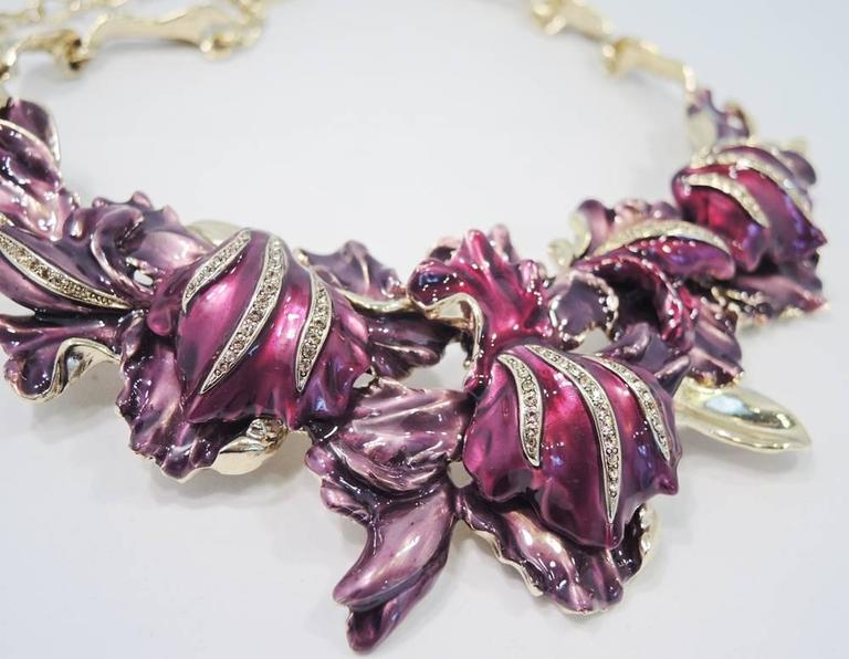 This Oscar De La Renta necklace features a floral orchid design with different shades of lavender and purple enameling accentuated with rhinestones.  In excellent condition, it is set in a gold tone setting and has a lobster clasp and measures 19""