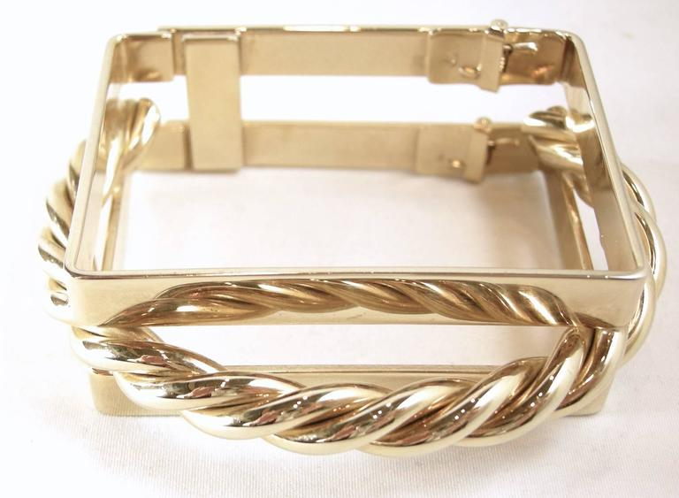 This bracelet has to be a designer piece.  It is so unique and looks like real gold.  It has a square shape with a gold-tone rope between 3/4 of the bracelet.  It has a hinge opening so it's put onto the wrist like a clamper bracelet. The photograph