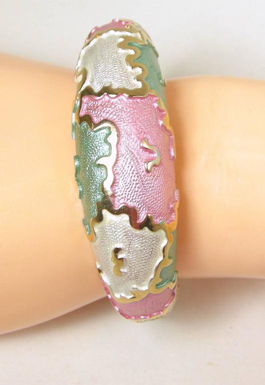 """This bracelet is perfect for the summer!  It has pink, silver white and iridescent blue enamel with a gold tone design border. It has a hinge with a slide in clasp and measures 8"""" x 3/8"""". It is in excellent condition."""