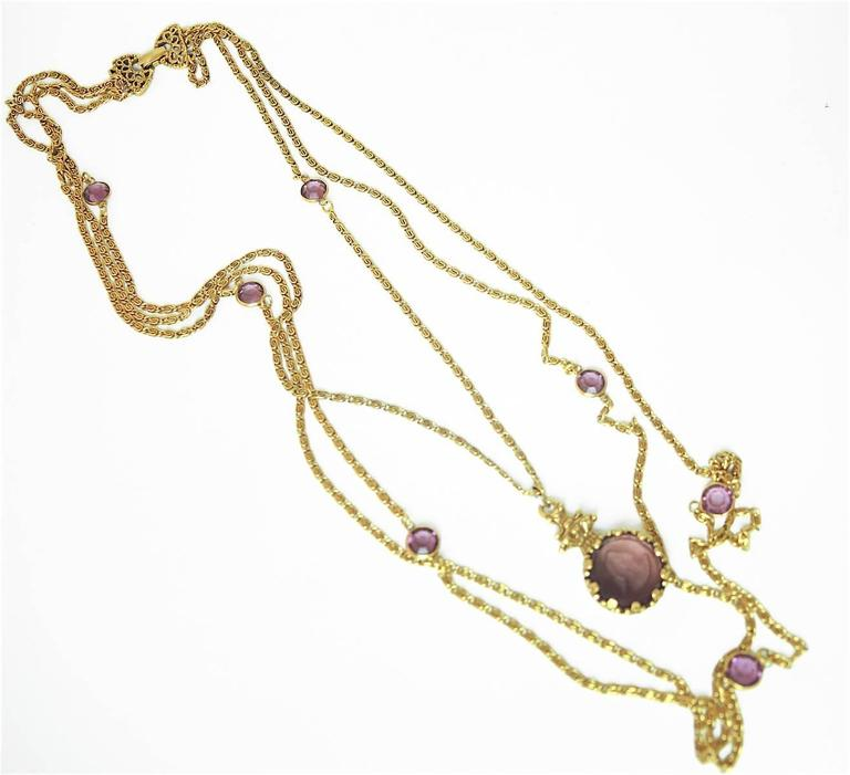 "This vintage 1960s Goldette necklace features one chain with a faux amethyst cameo pendant and two more chains with amethyst color discs in a gold-tone setting. The first chain with the cameo measures 24"", the second chain is 30"" and the third"