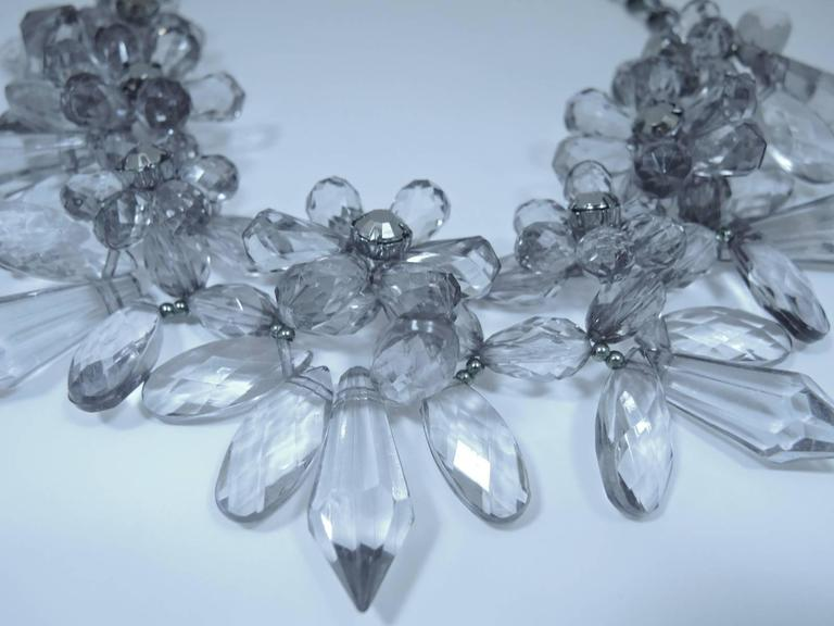 """This clear Lucite floral necklace will certainly catch the eyes of onlookers. It is made with oval and icicle shaped Lucite that are clear but have a grey undertone. The necklace is reinforced with a very strong wire and measures 22"""" x 3"""".  It has a"""