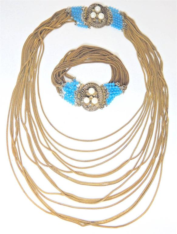 "This vintage Victorian necklace is layered with chains that graduate downward.  The necklace is accented with faux turquoise beads on both sides of an oval slide in clasp with 3 faux pearls set on golden leaves. The necklace measures 16"" x 1"".  The"