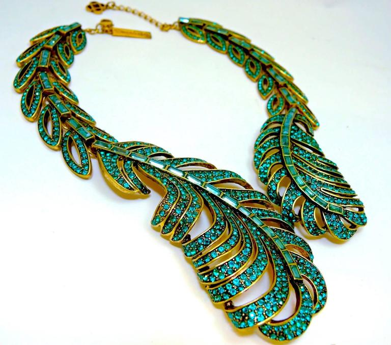 "This feather shaped Oscar De La Renta necklace gives these pave set and baguette green crystals a weightless appeal.  It is made in a gold tone setting and measures 19"" x 2-1/8"" at the widest part.  It has a lobster clasp and is signed ""Oscar De la"