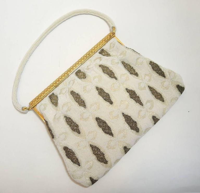 This stunning 1940s evening bag is in mint condition and is immaculately clean. Entire body is in white and gold small steel beads with a gold diamond shaped design on both sides. The gold tone flap has a basket weave design with rhinestones in the