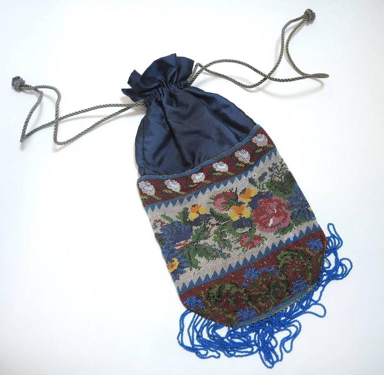 """I think the picture will best describe this lovely bag.  Here are some facts.  The purse  measures 11"""" in length  with a  2"""" fringe  and is  6"""" wide and is made with tiny steel beads.  It is in excellent condition.  I was told this multicolor floral"""