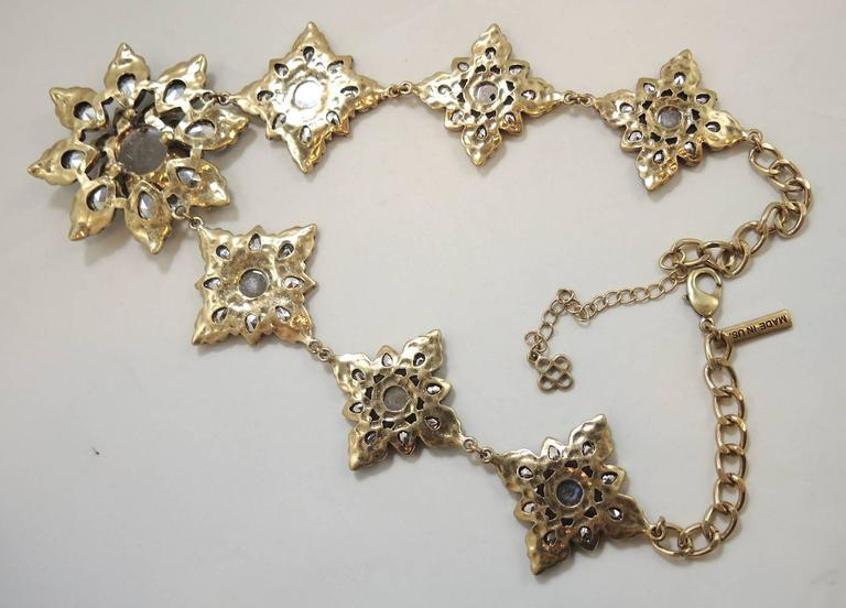 This lovely Oscar De La Renta necklace has seven snowflakes all made with smaller cobalt blue teardrops and round shaped rhinestones. The center of the largest snowflake has a periwinkle stone. It is made in a gold tone setting and has a lobster