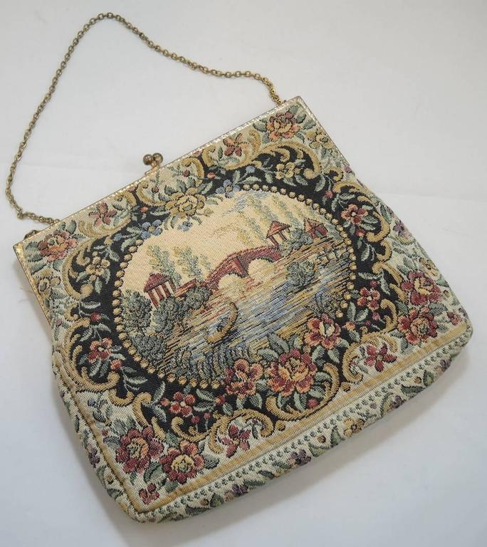 This is a special tapestry purse because it has survived throughout the years in mint condition. It has a picture of water flowing underneath a bridge framed with a floral design and has colors such as pink, beige, maroon and black. It is made with