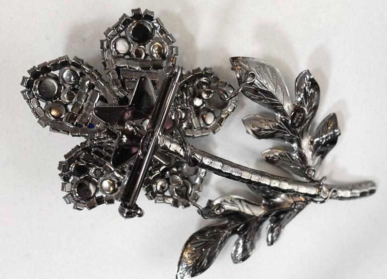 """This massive three-dimensional flower brooch was created by Lawrence Vrba. It is made with prong set faux turquoise stones, clear crystals and blue glass. It is in a gun metal setting and measures a whopping 6"""" x 4"""". It is signed """"Lawrence Vrba"""" and"""