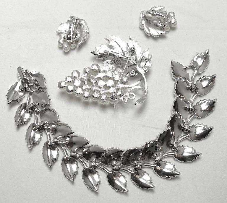 """This collectible 1950s Trifari set features a bracelet, earrings and brooch in a leaf design with faux pearl accents in a silver-tone setting. The bracelet measures 8"""" x 1-1/4"""" with a fold-over closure. The brooch has clusters of white pearls"""