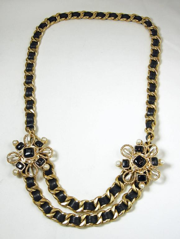 This is a special couture vintage Chanel necklace with Chanel's famous leather ribbon through the gold tone links. It has two layers at the bottom met by two floral black Gripoix squares and pearls spearing outward on each side. It has a hook clasp