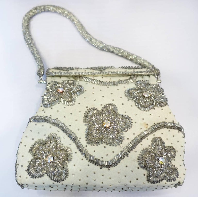 "This beautiful1960s hand bag is handmade and consists of gray & clear beads with aurora borealis stone accents on crème color cotton.  This handbag measures 7"" high x 8-1/2"" wide with a fold-over closure. The beaded strap is 5.5"" up from center."