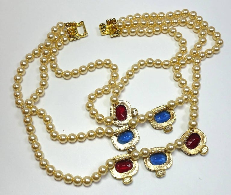 "This signed Kenneth Jay Lane multi-3-strand necklace features faux pearl with multi-color crystals in a nickel-free gold-plated base metal setting.  This necklace measures 16"" and the center falls approx. 3"" long and 3-1/2"" wide at the last"