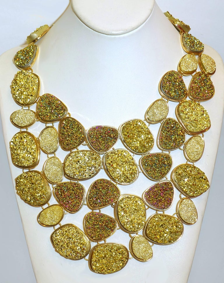 This is one of the one most unusual Oscar de la Renta's necklaces I have even seen.  It is created with different shades of green, iridescent pink and beige crystallized stones in various shaped disks designed in an extravagant bib necklace.  Each