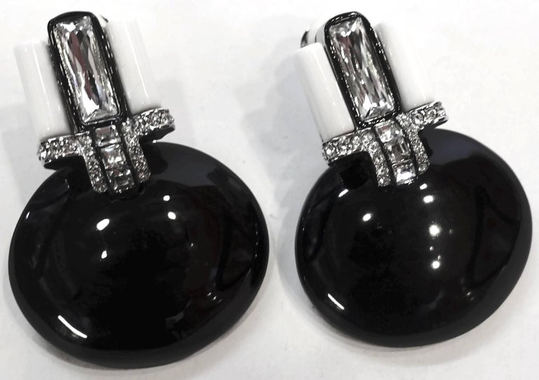 """These signed Kenneth Lane earrings feature faux onyx with white enameling with crystal accents in a silver-plated base metal setting. In excellent condition, these clip earrings measure 2"""" x 1-1/2"""" and are signed """"KJL""""."""