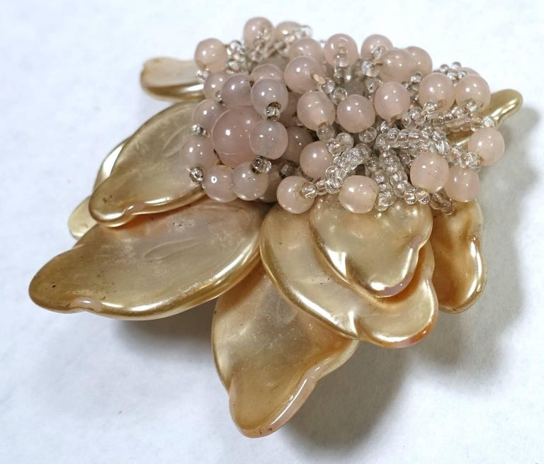It is so rare to find an early Haskell fur clip.  It was made in the early 1930s before she put her signature on.  But you can tell from the style and back that this is Haskell.  It is designed with faux pearl leaves with pink glass bead accents in