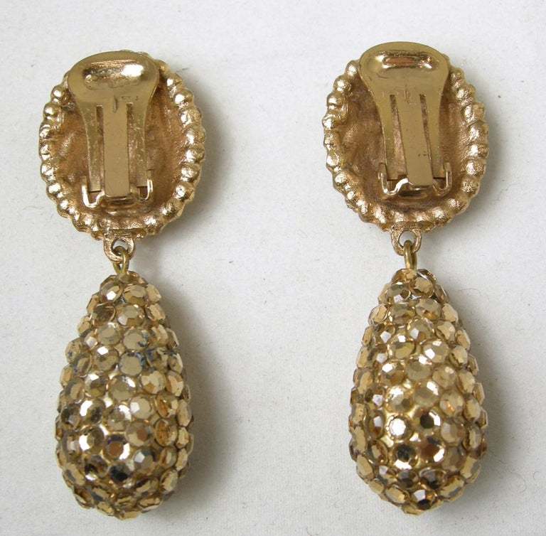"""When I first saw these clip earrings, I thought they were made by Richard Kerr.  It has the flat back gold tone rhinestones he was famous for.  These clip earrings have a round disk top with a large dangling drop.  It measures 2-1/4"""" long x 7/8"""""""