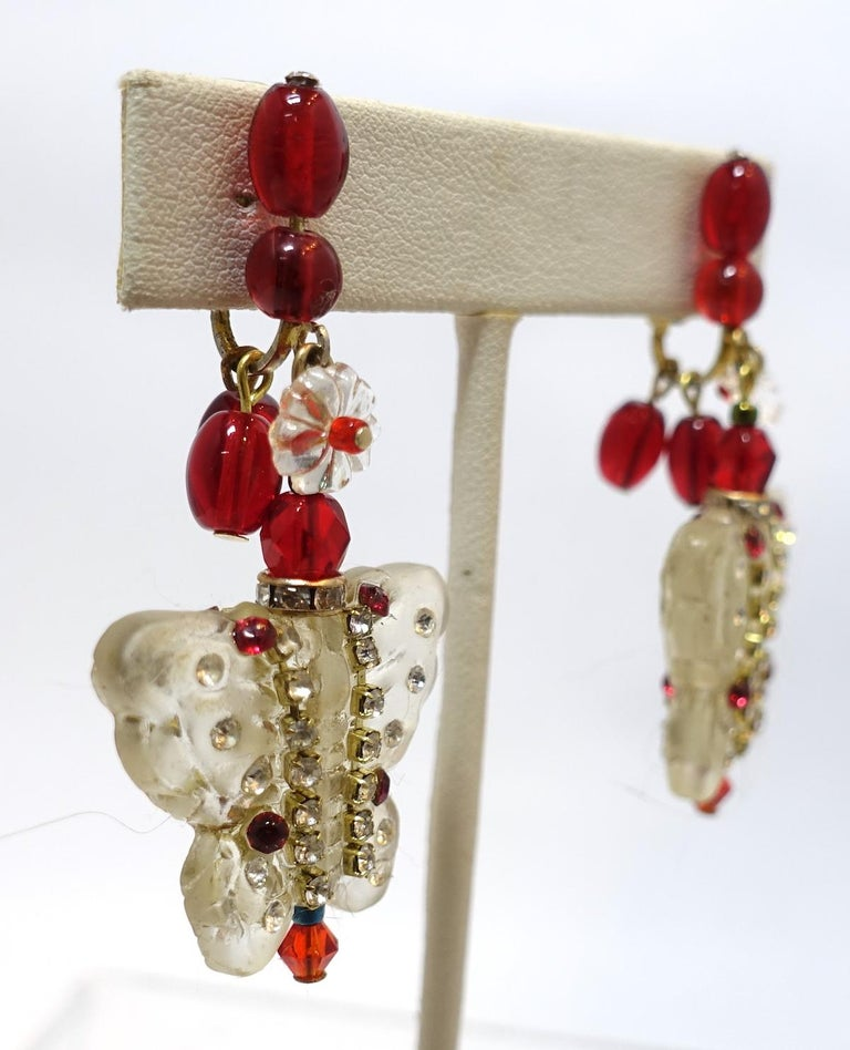 "These vintage 1950s earrings feature a Lucite butterfly drop with red and clear crystals and red bead accents in a gold tone setting.  These clip earrings measure 2-1/4"" x 1-1/8"" and are in excellent condition."
