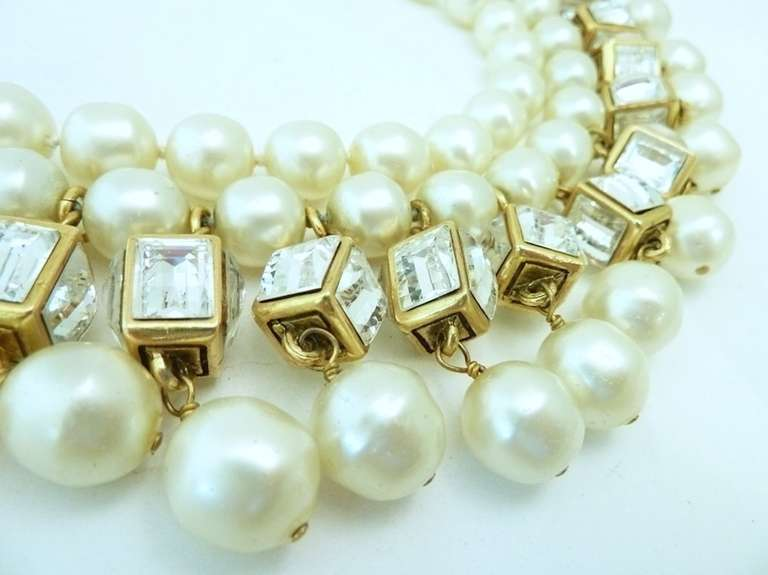 This vintage museum piece is marked season 23 which makes it early 70's or late 60's.  This vintage signed Chanel necklace features two strands of faux pearls with rhinestone-accented cubes in a gold-tone setting. It is visually a masterpiece and
