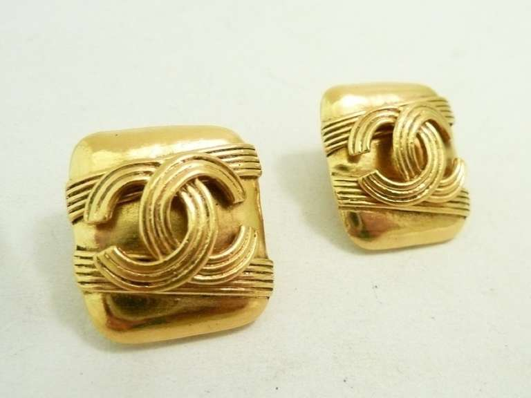 """These vintage signed Chanel earrings features the CC logo in a gold-tone setting.  In excellent condition, these clip earrings measure 7/8"""" x 15/16"""" and are signed Chanel 94A Made in France."""