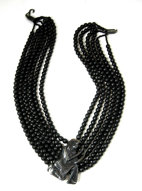 "This vintage signed Hattie Carnegie necklace features 12 strands of black beads with an ornate Egyptian style centerpiece. This necklace measures 19-1/2"" with a hook closure and the centerpiece is 2"" x 1-1/2"" and is signed ""Hattie"