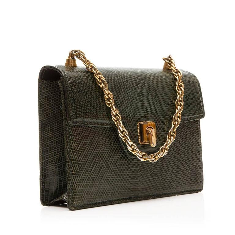 Gucci vintage handbag in olive green lizard skin featuring a flip lock detail and gold- tone chain. The interior of the bag is lined in dark brown leather and boasts three open pockets and one zipped pocket. This bag can be carried in hand or over