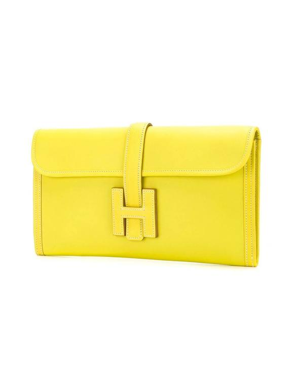 Yellow Swift leather embossed logo clutch from Hermès featuring a rectangular body, a stitch detail, a foldover top, a strap closure and a main internal compartment.   Colour: Yellow (Sulphur)  Material: Swift Leather  Measurements: W: 29cm