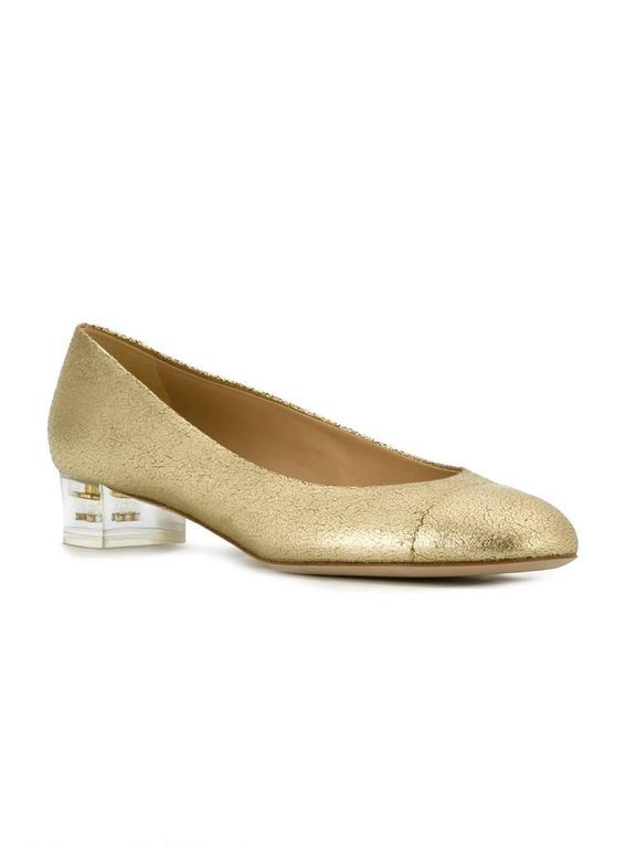 Gold-tone leather transparent heel pumps featuring an almond toe, a branded insole, a low block heel and a signature toe cap detail. 