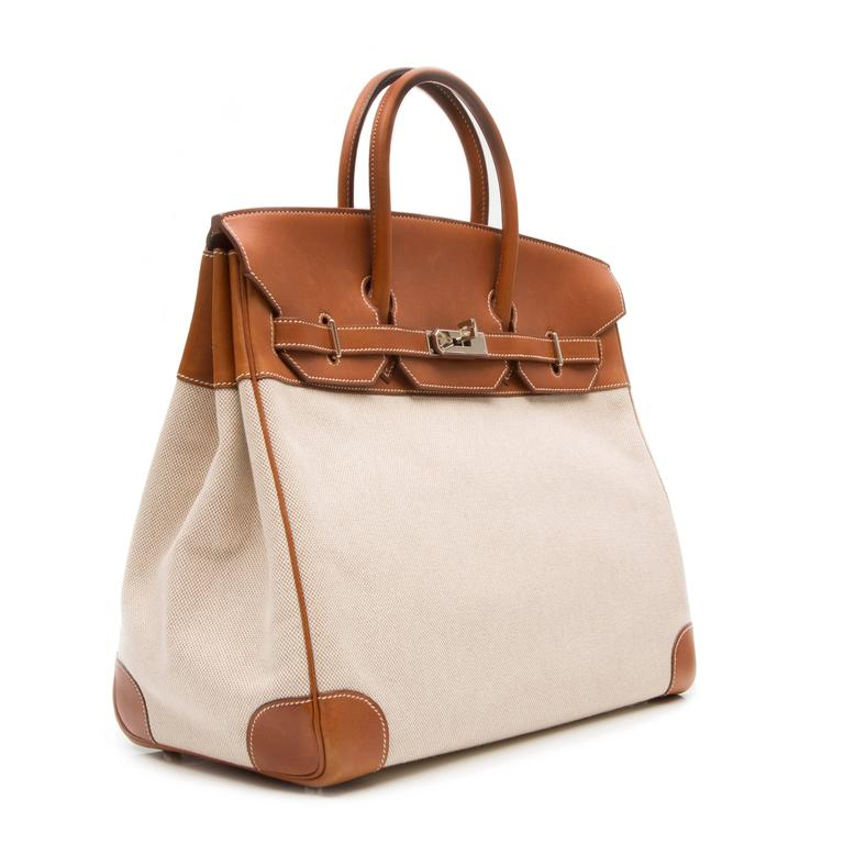 Brown cotton and leather 'Birkin' tote featuring a foldover top, a round top handle, a silver-tone twist lock fastening, stitching details, a hanging luggage tag, an internal zipped pocket and an internal patch pocket.   Colour: Brown  Material: