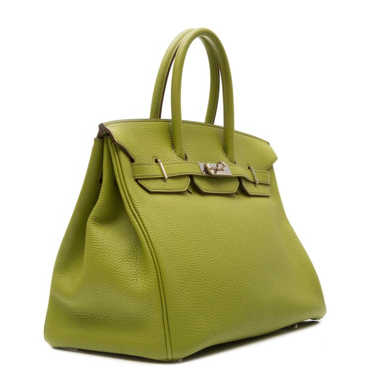 Green leather 'Birkin' tote featuring a trapeze body, round top handles, foldover top with twist-lock closure, a pebbled leather texture, silver-tone hardware, a padlock fastening detail, a hanging key fob, an internal zipped pocket and purse feet.