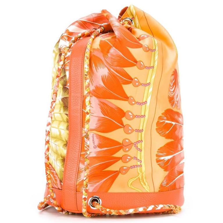 Exude tropical fantasies with this vintage Hermès backpack. A sun-soaked pattern in shades of orange and green features across the bag's drawstring profile. It is printed with the word Brazil, and the Hermès logo. The backpack straps are woven,