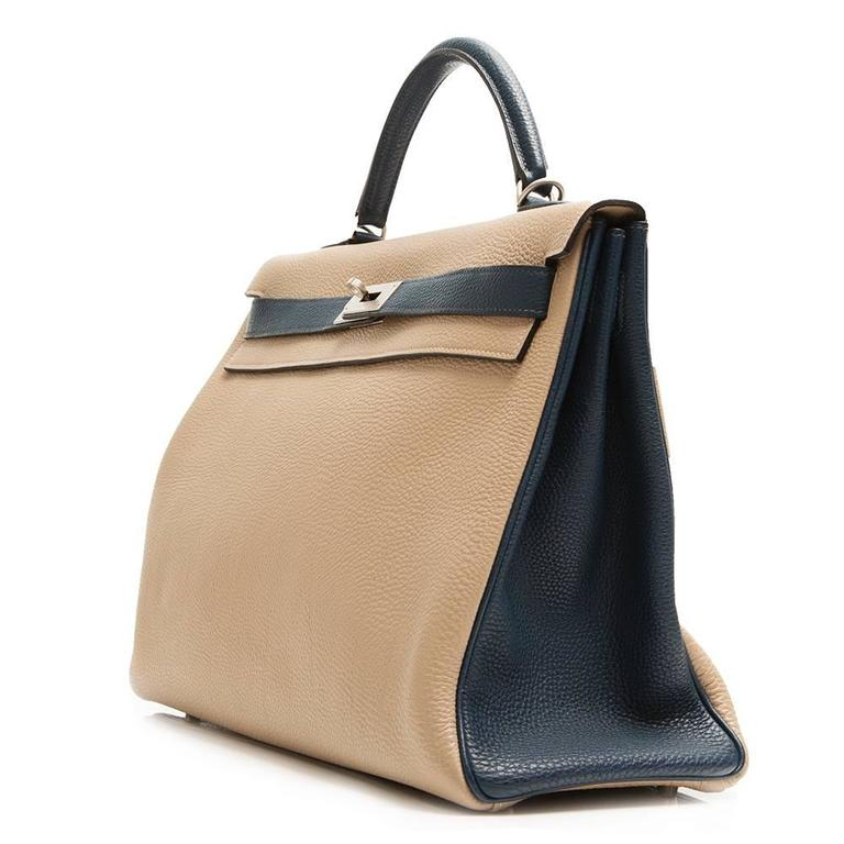 This Hermès Kelly 40 bag is rendered in an elegant bi-tone that complements its ladlylike silhouette. An Etoupe body – a grey-toned beige – is offset with Blue de Galice handles, belt arms and piping. It is crafted in Togo leather, a popular