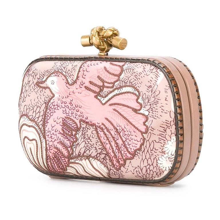 A romantic reimagining of Bottega Veneta's iconic Knot clutch. The facade hard-case bag is adorned in an embroidered textile that is printed with an pink-toned illustration of a bird. This is off-set with the brand's knotted Intrecciato clasp in