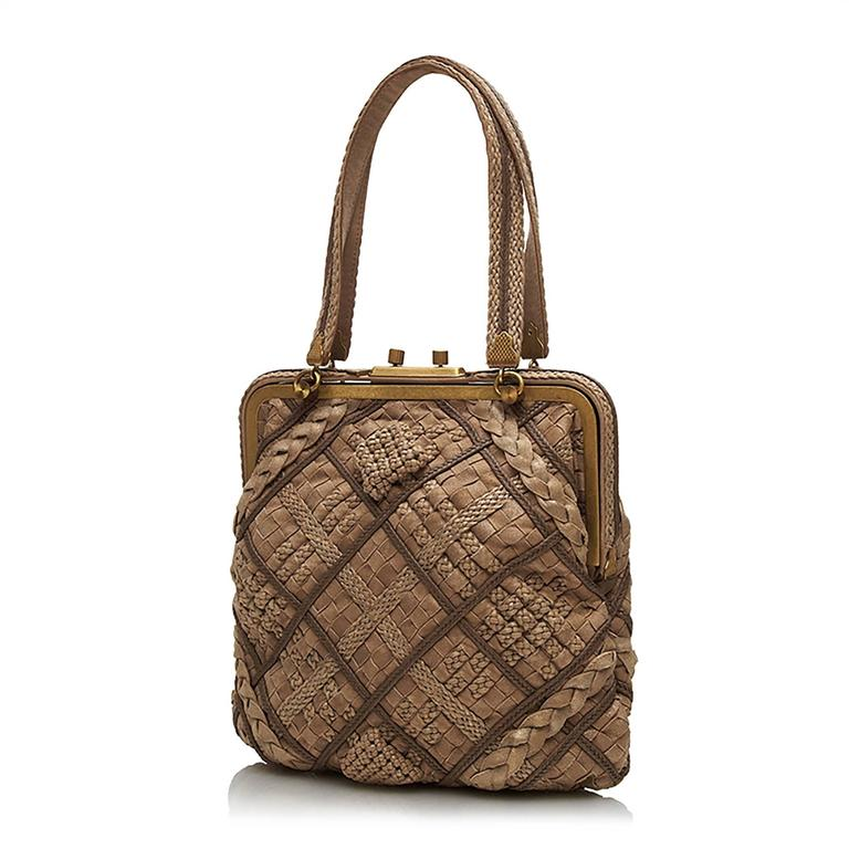 Bottega Veneta's signature Intrecciato woven leather is here rendered in an exquisite, brown square-shaped clutch. Its braided, patterned design exudes the artisanal aesthetic inherent to the Italian fashion house. This is luxuriantly offset by a
