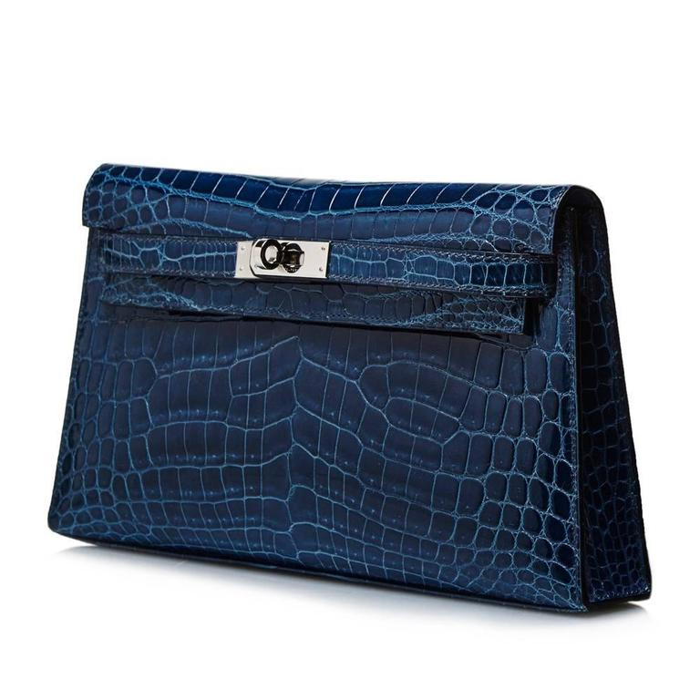 This Hermès Kelly Elan clutch is strikingly rendered in Bleu Petrole Nilo crocodile skin. It features the angular style lines of the iconic Hermès Kelly tote bag, as well as its twist-lock closure, here finished in palladium.  This item arrives