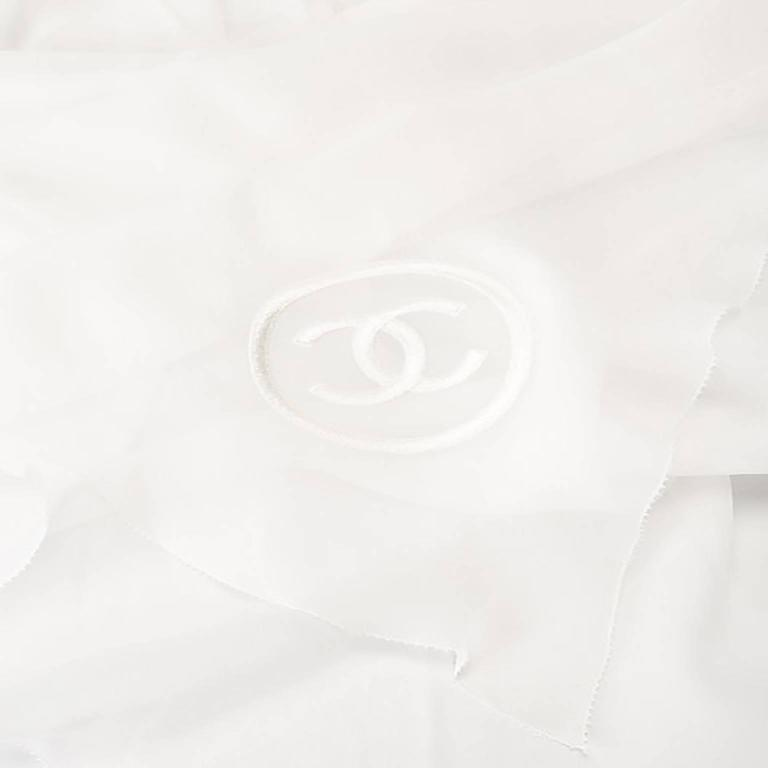 Utterly feminine, this Chanel scarf is rendered in a floaty, ivory silk. Its pleated silhouette tapers at the middle for a flattering effect when wrapped around the neck. The scarf features an embroidered Chanel monogram in tonal ivory