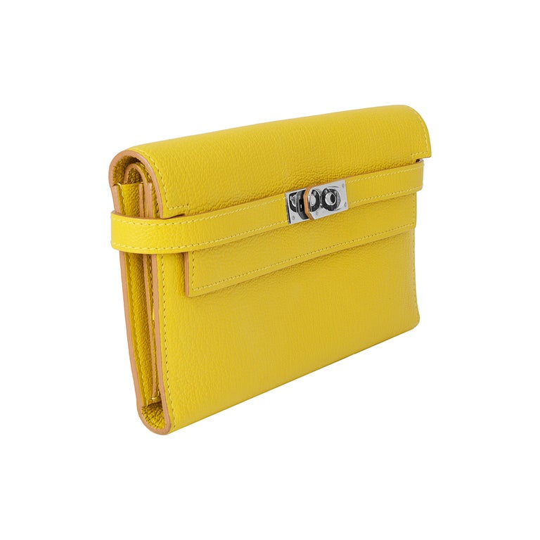This striking cumin yellow wallet is the perfect bold accessory. Open the palladium Hermès closure on the flap to the leather lining with a center zipped section, a space on either side, two long sections, and twelve credit card slots.   Colour: