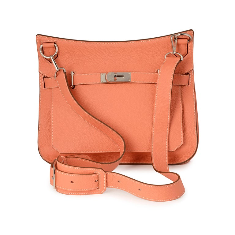 This luxurious Hermes messenger bag is crafted from Clemence leather featuring a front flap closure with the iconic Hermes turn-lock clasp closure and palladium hardware accents. This opens to a roomy coral leather-lined interior with front zip