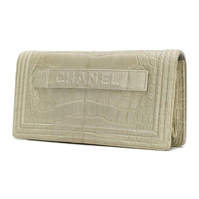 Crafted from beige crocodile leather, this stunning Chanel clutch bag features a foldover top with a silver-tone logo closure, a hand strap, an internal zipped pocket and embossed logo plaque.  This bag comes with a Chanel Care Guide and