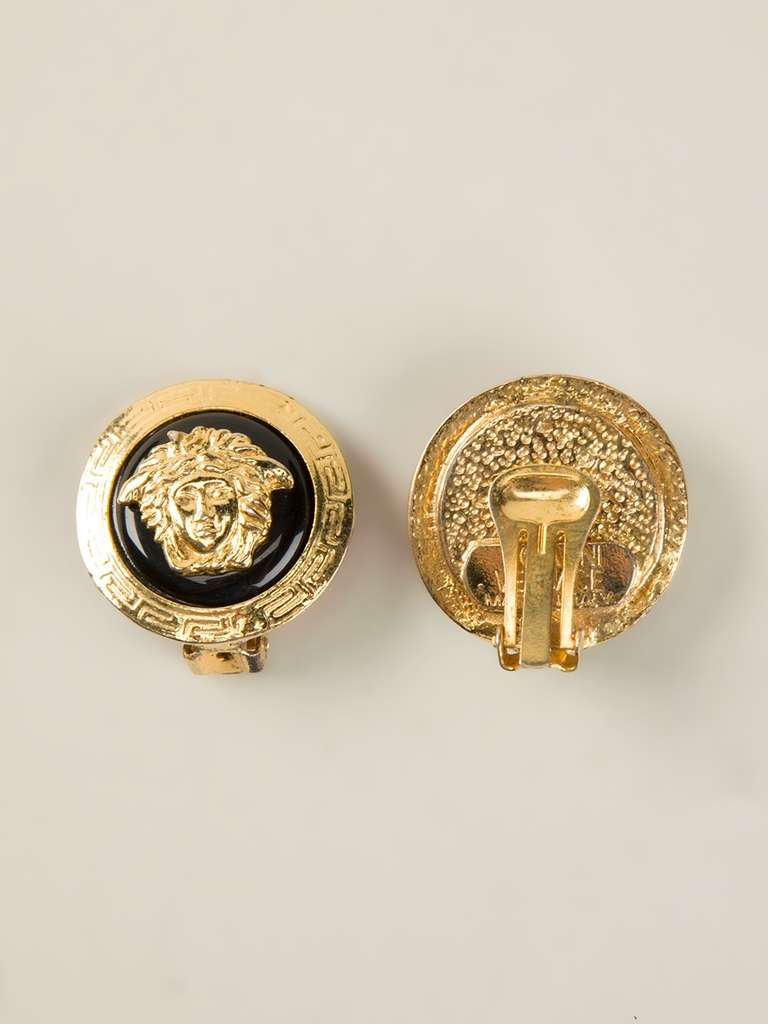 Gold plated Medusa clip-on earrings from Gianni Versace Vintage in a round shape and featuring the popular Medusa logo over a contrast black background.