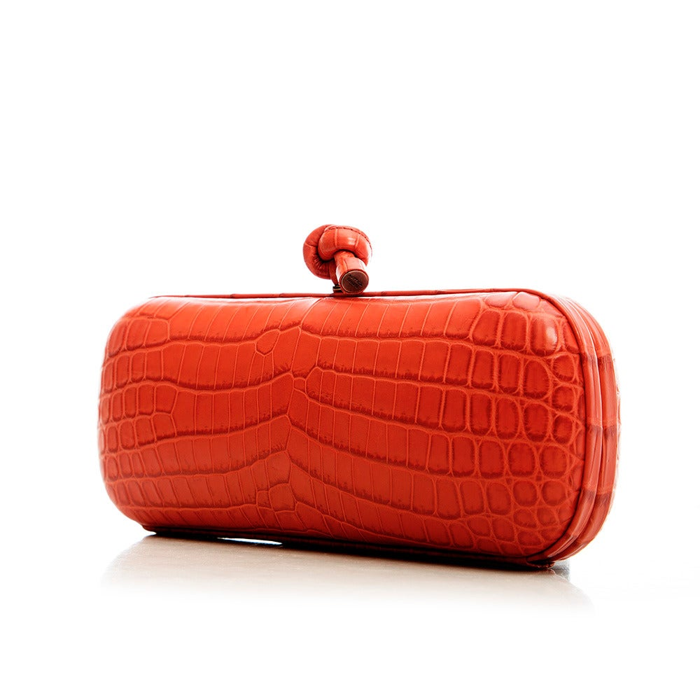 This alluring clutch from Bottega Veneta features a croc leather body with leather trim and a logo detail clasp.  Material: Crocodile leather Measurements: width: 25 cm, height: 11 cm, depth: 8 cm Colour: Red Condition: 9 out of 10 Excellent