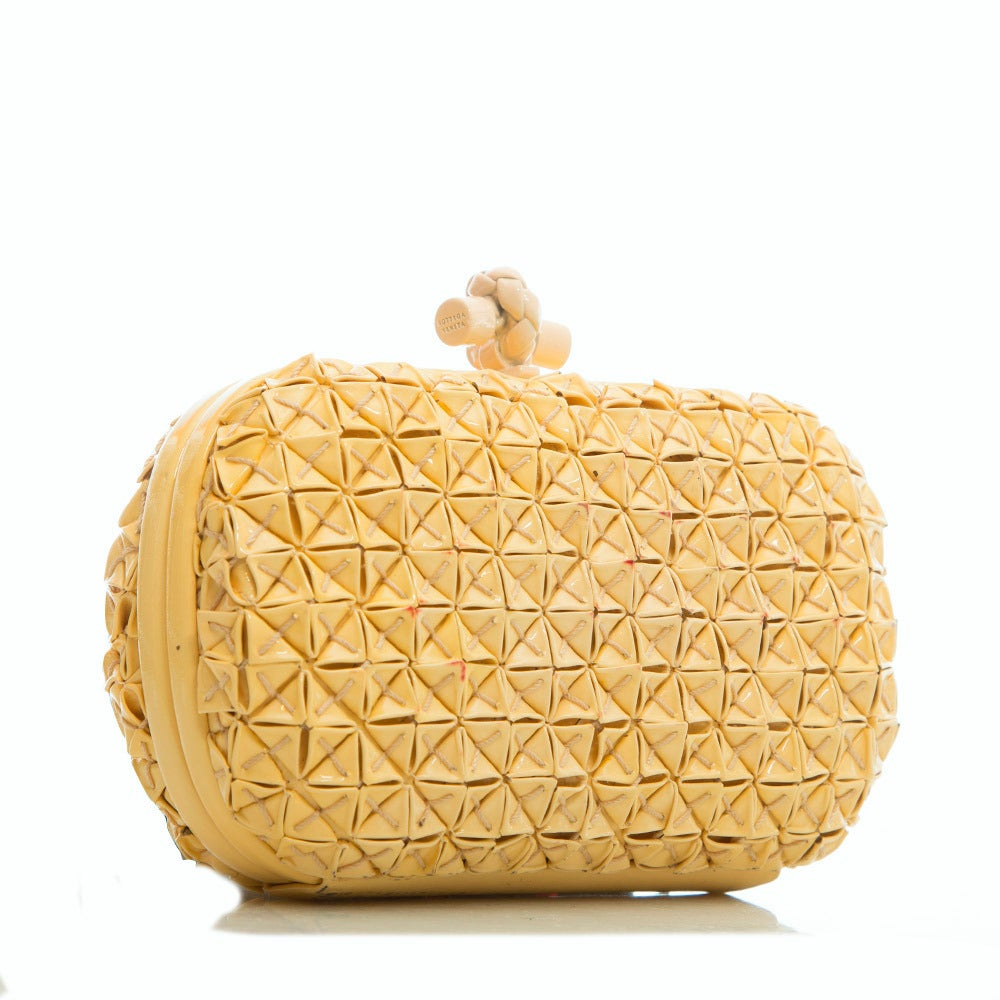 This playful clutch from Bottega Veneta features a textured PVC body and a logo detail clasp. The contrast lining is crafted in pure leather.