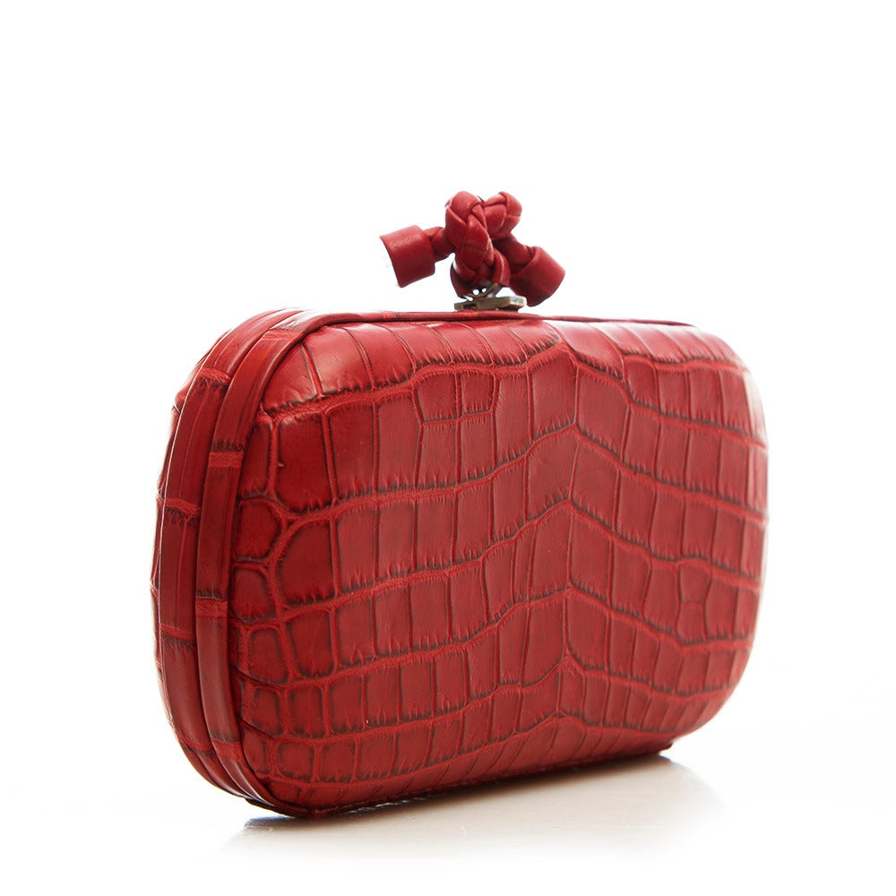 This alluring clutch from Bottega Veneta features a croc leather body, textured metal hardware at corners and a logo detail clasp. The contrast lining is crafted in pure suede.