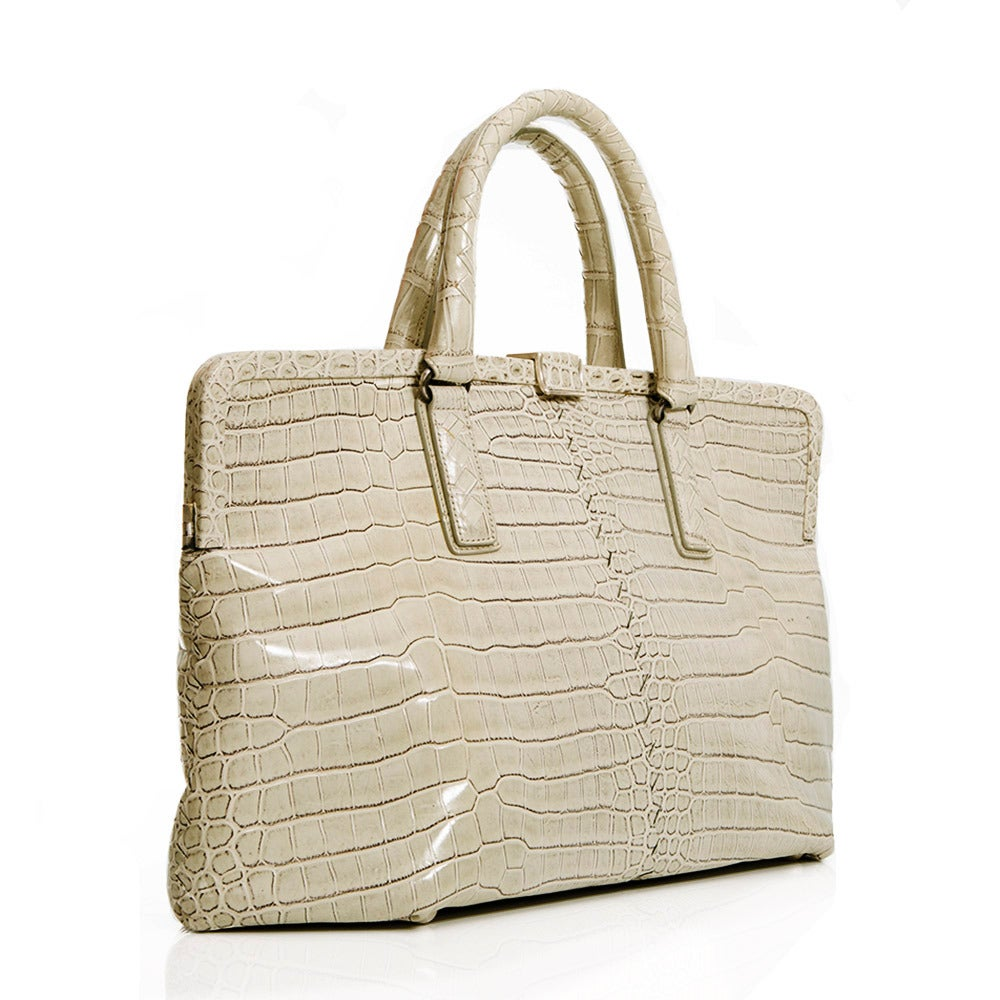 Featuring an exquisite crocodile skin in beige , this handbag from Bottega Veneta is complimented by silver hardware on the handles and clasp and a hexagonal opening. This piece has a large interior along with an internal zip-compartment and
