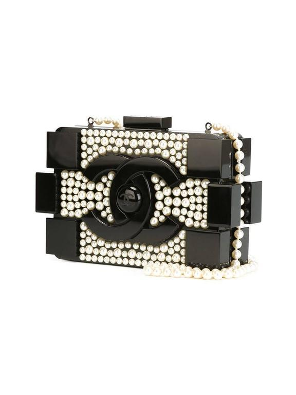 Black Brick pearl clutch featuring a front embossed logo stamp, a magnetic fastening, an interior zipped compartment and a pearl shoulder strap.  Colour: Black and White  Material: Plastic 100%  Measurements: W: 20cm,H: 11.5cm, D: 5cm, Strap: