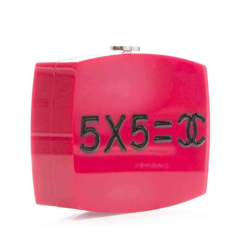"""The standout pink bag features a simple math equation """"5x5=CC"""" on one said while the other side has the quote """"Je Ne Suis Pas En Solde"""" (I Am Not For Sale). The feminist plexiglass bag includes palladium hardware, a chain link with navy blue leather"""