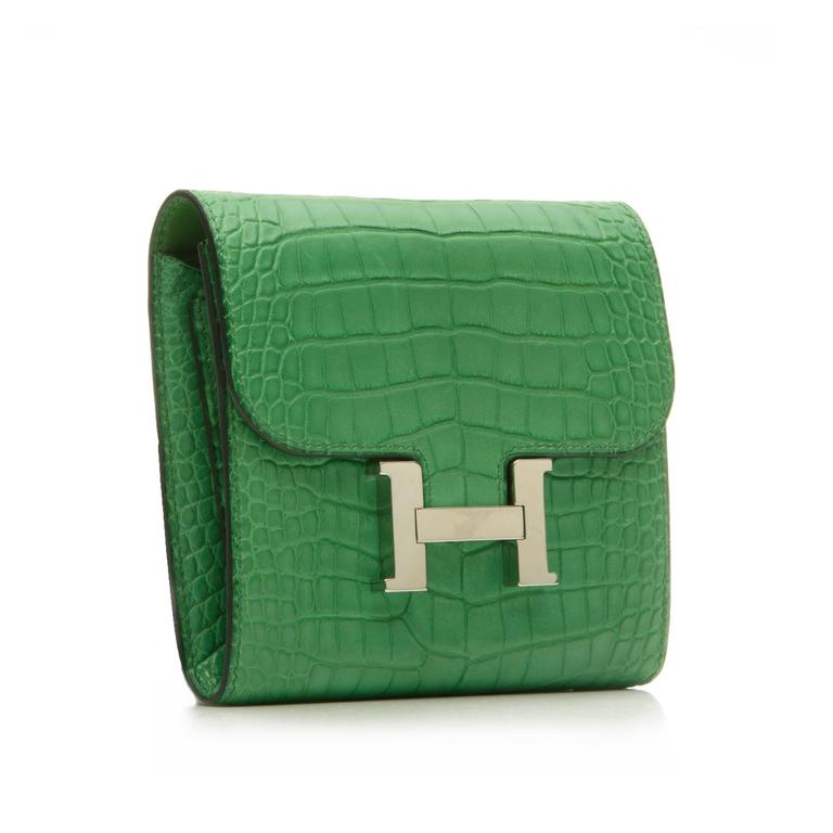 A bold design for organising monetary essentials, this Hermès Constance wallet is crafted in a Cactus green alligator skin offset with palladium hardware. Featuring the iconic Hermès Constance logo fastening, a back slip pocket, several interior