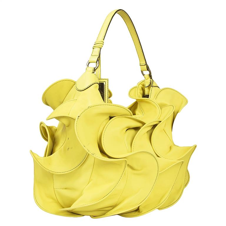 A joyful creation from Valentino brimming with the romantic fantasy at the heart of the brand. This handbag is formed from ripples of yellow leather. Its black-lined interior contains one zipped pocket and two open pockets.  Material: