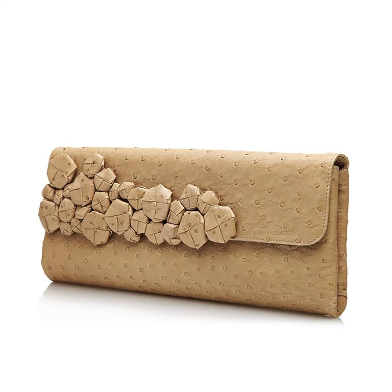 An exquisite envelope clutch by Bottega Veneta, the Italian fashion house so revered for its extraordinary quality of craftsmanship. This rare piece features a beige ostrich skin exterior. Among the most premium exotic leathers, ostrich skin is