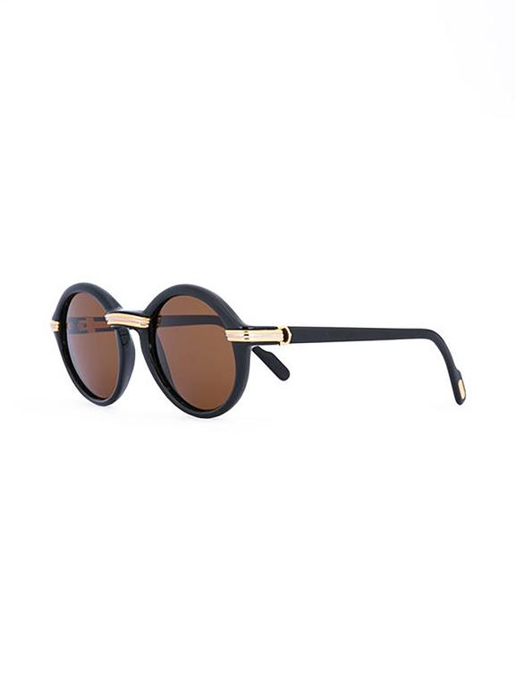 Cartier elevates a classic silhouette with these acetate sunglasses. Black lenses and frames are accented with a shimmer of gold tones along the bridge, the temples, and the arms.   This item includes its original leather Cartier sunglasses