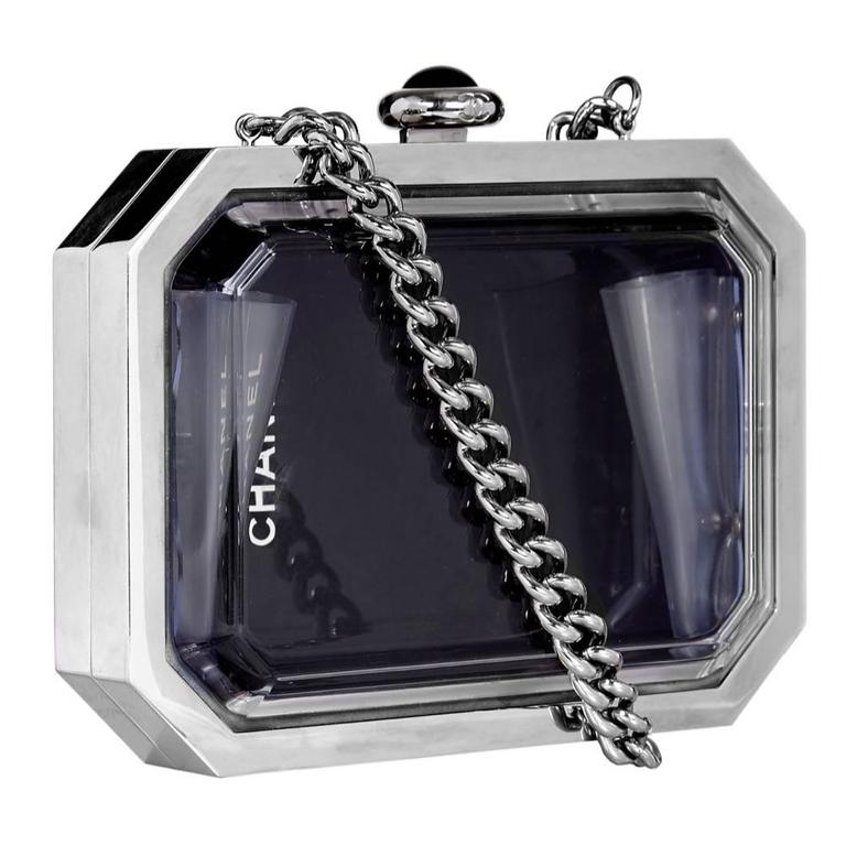 This vintage Chanel minaudière is crafted from mirrored hardware in sleek style lines. Panelled with plexiglass, one side is glossy black and the other is transparent - you can even see a Chanel logo through the window.  It's topped with a